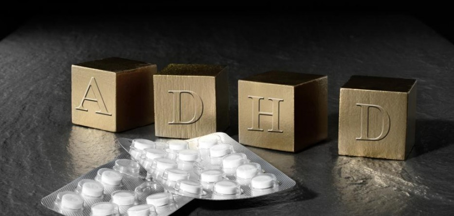 Creative concept image for Attention Deficit Hyperactivity Syndrome or ADHD. Gold wooden blocks and medication tablets against a black background. Copy space.