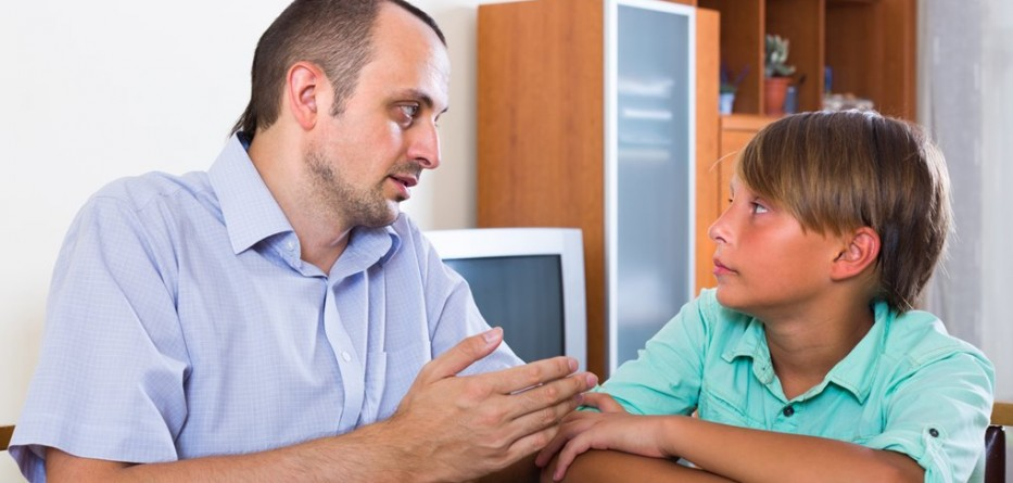 Portrait of father and his teenager son having serious conversation at home