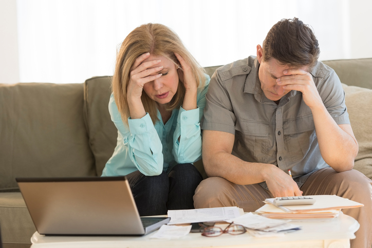 Worried mature couple calculating home finances on sofa