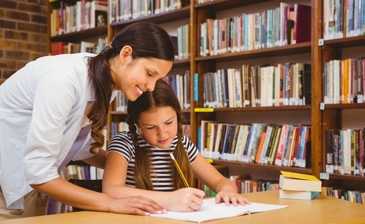 Teacher assisting girl with homework in library