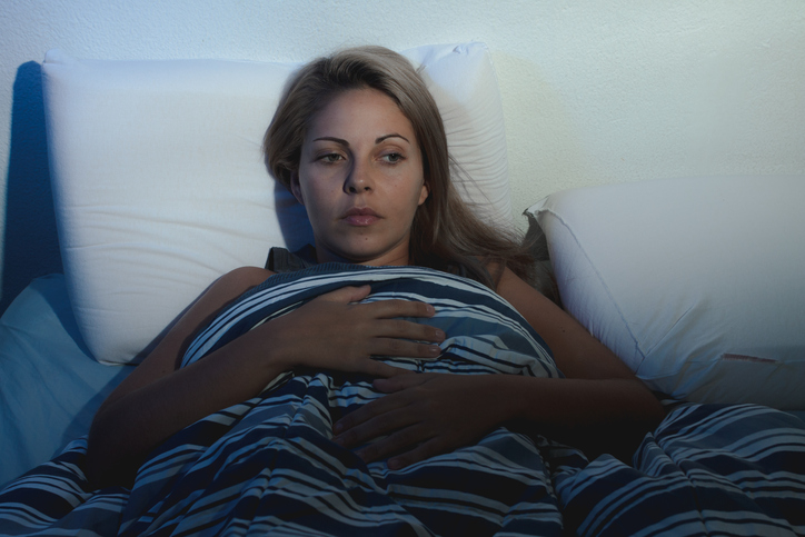 Insomnia. young blonde woman lying on the bed awake