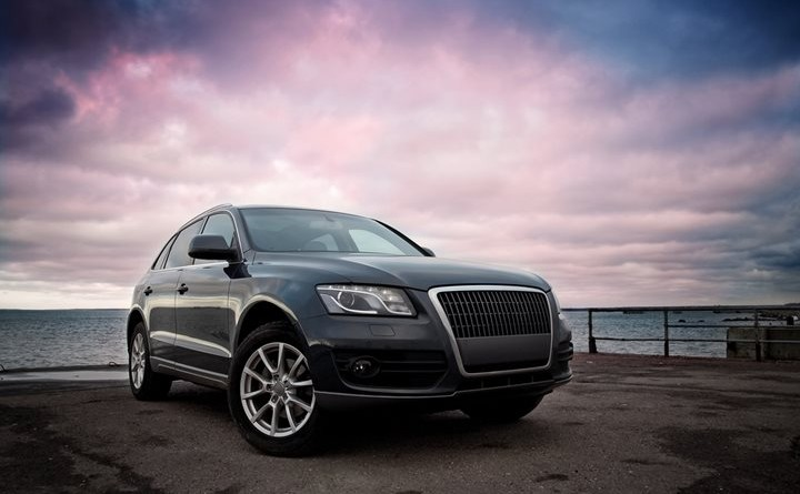 Luxury SUV near the sea with dramatic sunset sky