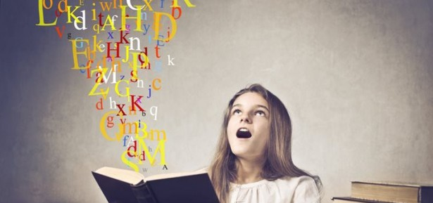 Astonished teenage girl reading a book