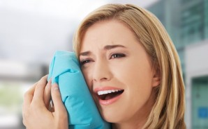 Woman having tooth ache holding ice bag near face