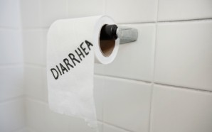 Close-up of toilet paper roll with diarrhea written in bathroom