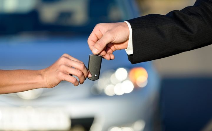 Car salesman giving key to female buyer. Vehicle sales or rental concept.