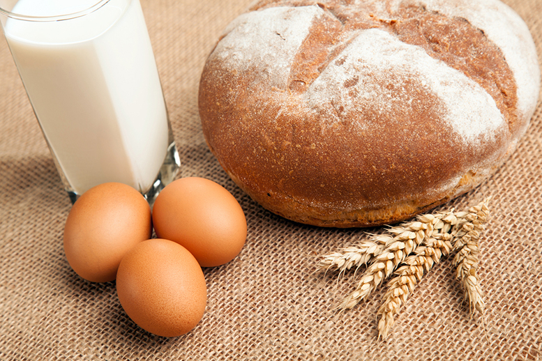 Eggs, bread and glass of milk on rustic table-cloth